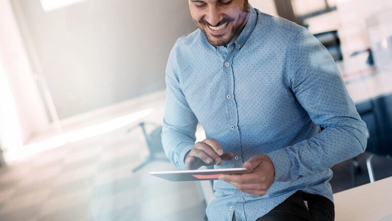 tech - happy man in blue using tablet reader