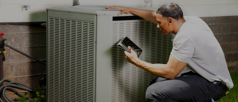 Man resting arm on air conditioner
